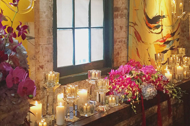 Candles and flowers on side table inside of Arta Gallery venue in Toronto
