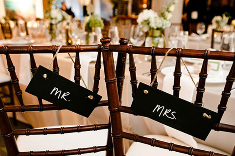 Mr and Mrs signage hanging from chairs for a wedding at Arta Gallery