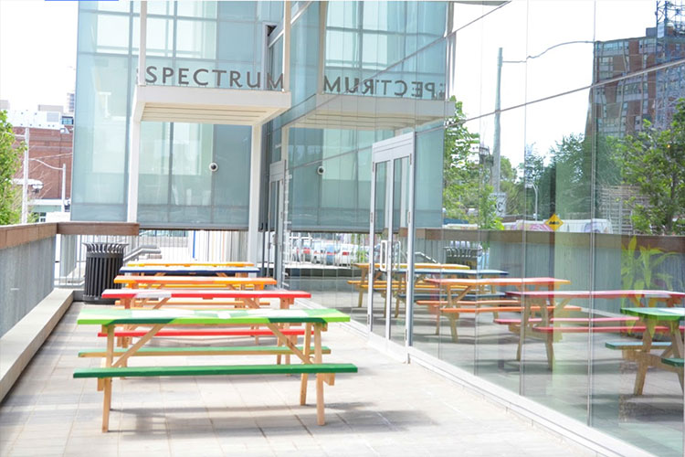 Patio with colourful picnic benches outside of Artscape Daniels Spectrum venue