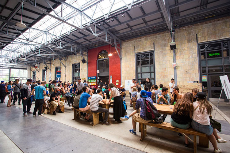 People sitting and talking on benches inside Artscape Wychwood Barns venue space