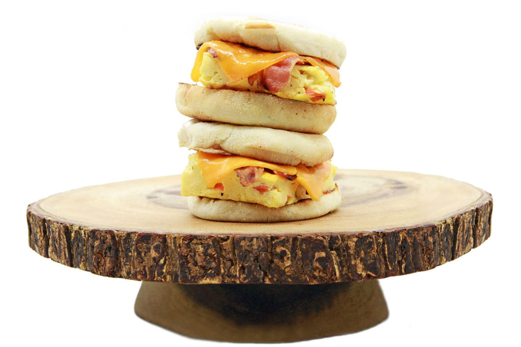 Bacon egger sandwiches on a round wood display board