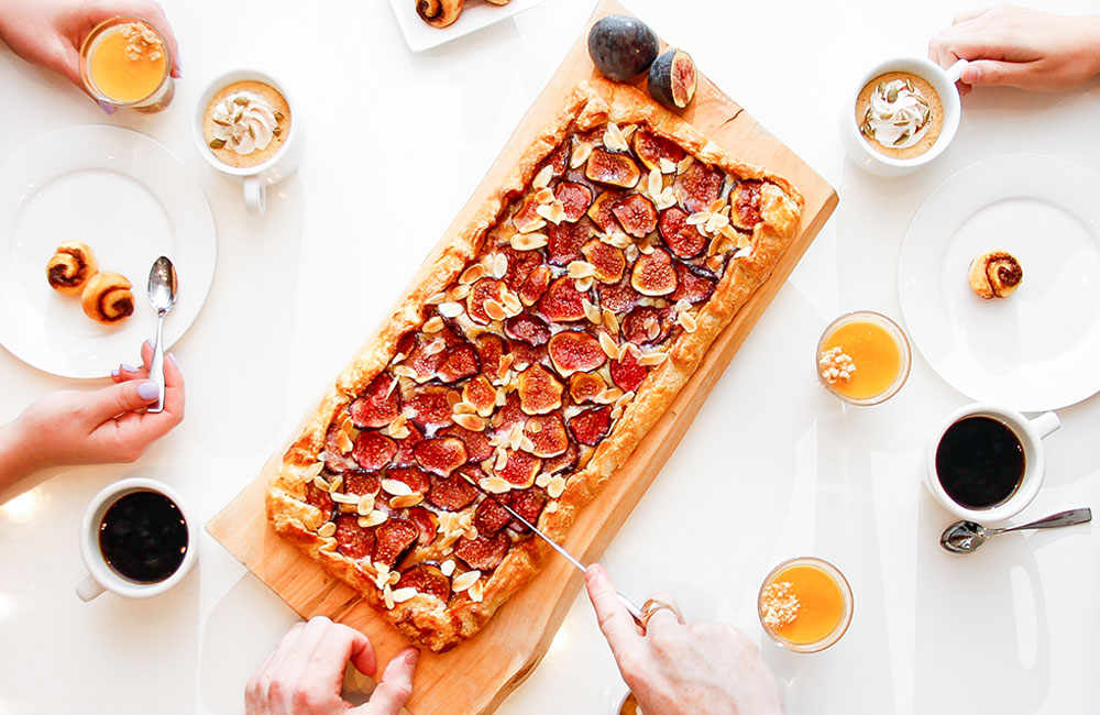 Group of people at a table eating fig pizza with coffees