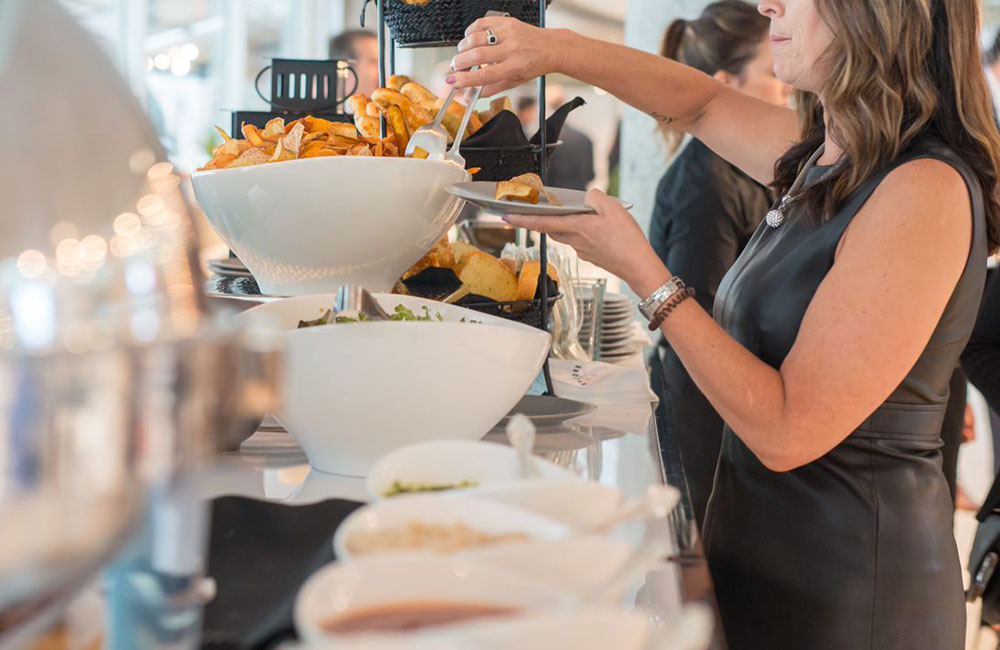 Employee taking food from buffet at catered lunch