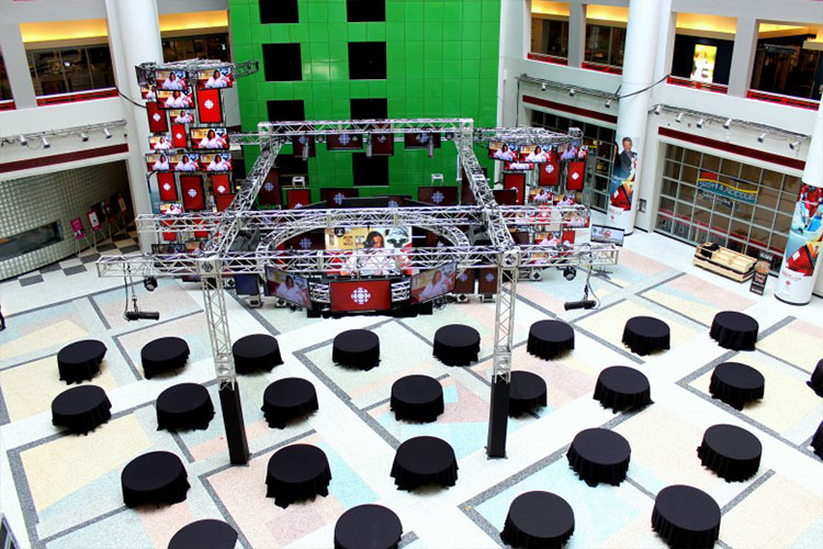 View of CBC Atrium from high up looking at black circular tables in main atrium