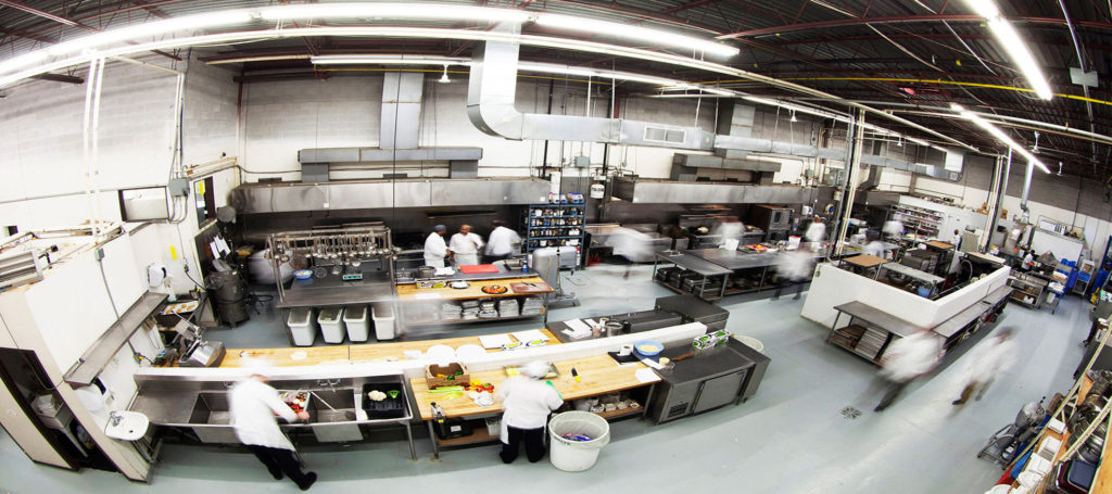 Panoramic view of Encore Catering kitchen with staff working