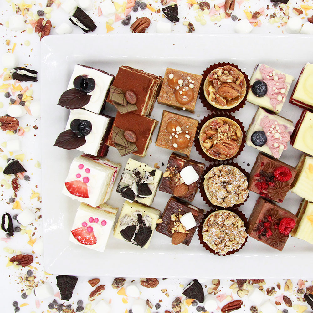 Birds eye view of various flavours of dessert snacks including dessert squares and tartlets