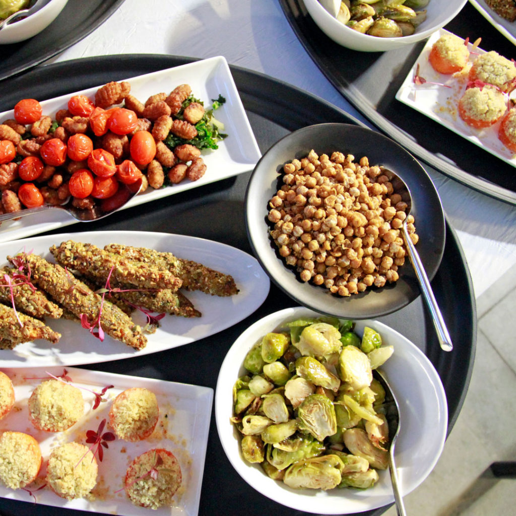 Family style dinner ready to be served at a wedding with chickpeas, brussel sprouts, and more dishes