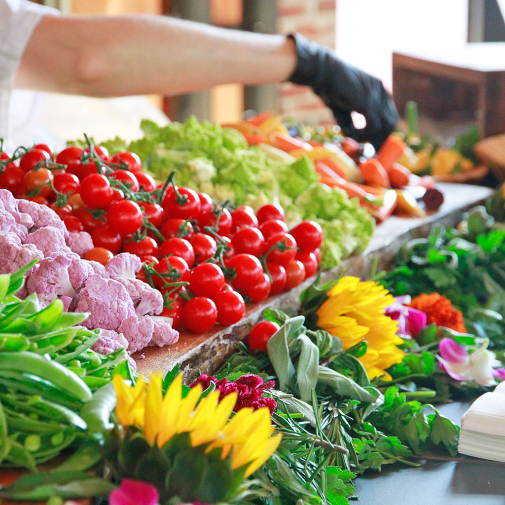 Harvest table display with tomatoes, purple cauliflower, broccoli, carrots and more vegetables