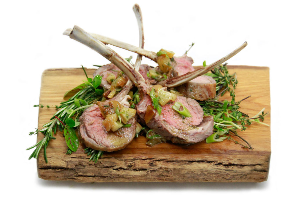 Herb crusted rack of lamb with apple mint chutney plated on wood display board