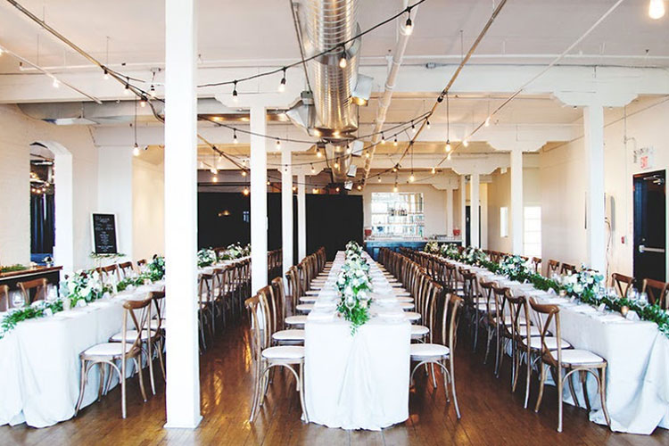 Three long tables with chairs and flowers for fancy wedding at The Burroughes venue space