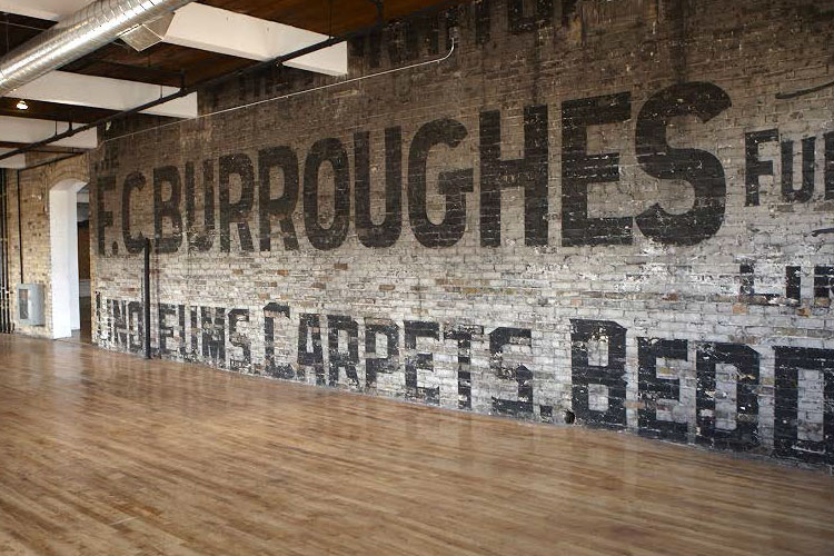 The Burroughes brick wall inside of the venue space with hardwood floor