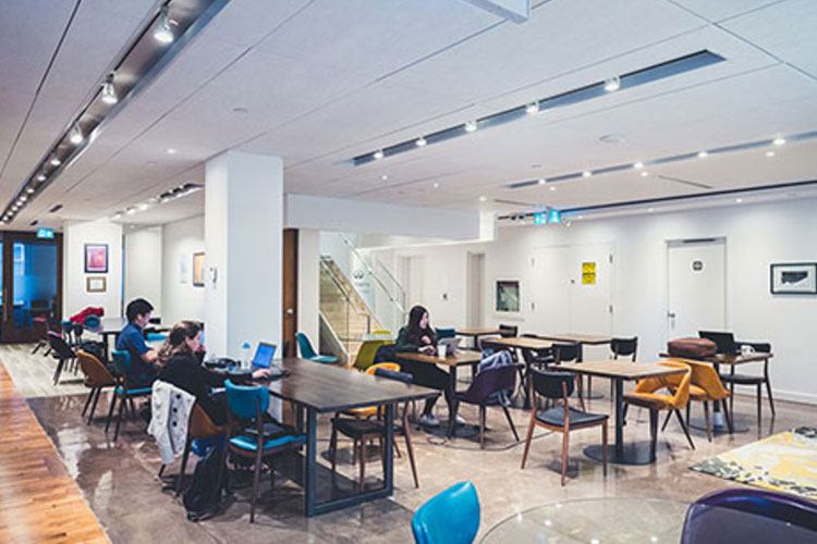 People working at tables inside of a Workhaus workspace